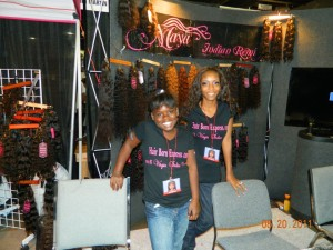 """Maya"" banner and hexagon shaped hang tags (background). Plus womens t-shirts on display at Bronner Bros. Hair Show, Atlanta"